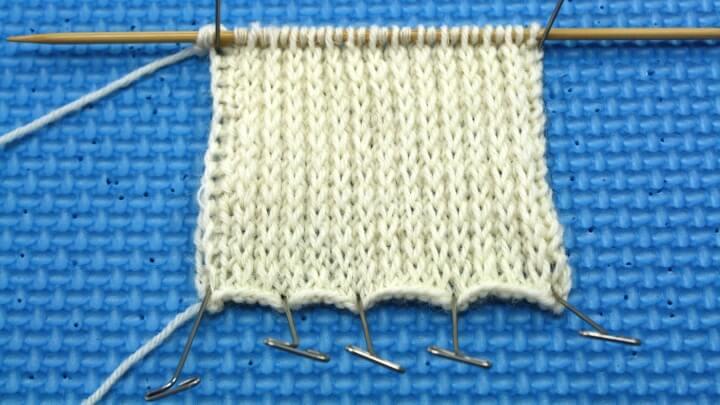 Bei der verstärkärkten Fersenwand wird in der Hinreihe wie folgt gearbeitet: 1 Masche mit hinten liegendem Faden links abheben, 1 Masche rechts. Diese Schritte fortlaufend wiederholen. Die Rückreihe wird links gestrickt.